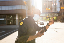 Security Guard Wearing Facemask Hailing Taxi In City Center