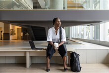 Thoughtful Businesswoman With Coffee In Modern Office Lobby