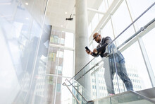 Businessman In Suit Using Smart Phone At Railing In Modern Office