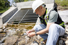 Environmental Inspector Checking Water Quality In Drain