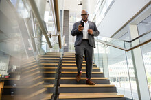 Businessman In Suit With Smart Phone Descending Stairs In Office