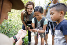 Family Taking Photo Of Caterpillar On Ranger's Hand Caterpillar In For