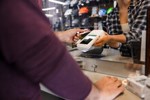 Customer Touching Credit Card On Terminal Held By Manager