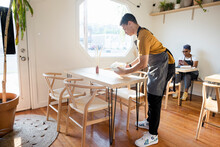 Waiter Cleaning Up Table In Cafe