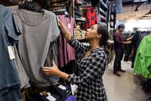 Customer Looking Teeshirts In Clothing Store