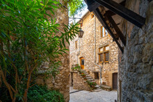 A Narrow Cobbled Road And A Covered Walkway In The Medieval Walled City Of Tourrettes Sur Loup, France.
