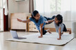 Asian young mother and her daughter doing stretching fitness exercise yoga together at home. Parent teaching child work out to be strong and maintain physical health and wellbeing in daily routine.