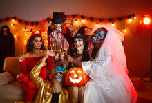 Group Of Cheerful Friends In Spooky Halloween Costumes Posing With Glasses Of Champagne In Hands. Multiethnic Young People Celebrate Halloween At Home In Room With Holiday Decorations And Red Lights.