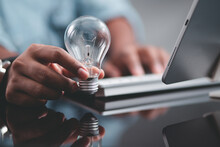A Business Man Sitting In Front Of A Laptop Holding A Light Bulb In His Hand Presenting Ideas Based On Technology Concepts.