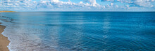 Panoramic Seascape With Gentle Waves Rolling In On The Beach In The Atlantic Ocean In Massachusetts