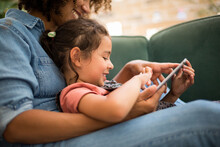 African American Mother And Daughter Watching Entertainment On Digital Tablet At Home