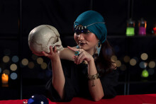 Dark Witch Casting A Spell On Skull, Mysterious Magnificent Beautiful Woman In Black Dress Holding And Pointing At Human Skull
