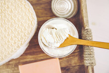 Bodywhip Also Known As Body Butter, Skin Care Moisturizer Cream On Wood Spoon And Jar On Natural Wooden Tray With Bath Sponge And Candle.