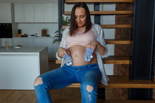 Smiling Pregnant Woman In Pink Top And Jeans Shows Cute Socks For Future Kid Sitting On Wooden Ladder Against Stylish Room