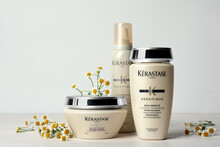 MYKOLAIV, UKRAINE - SEPTEMBER 07, 2021: Set Of Kerastase Hair Care Cosmetic Products And Chamomile Flowers On White Wooden Table