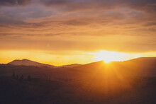 Atmospheric Landscape With Silhouettes Of Mountains With Trees On Background Of Dawn Sky With Sun Circle And Orange Sun Rays. Colorful Nature Scenery With Sunset Or Sunrise Of Illuminating Color.