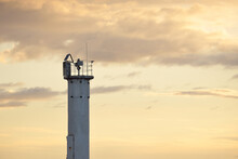 Lighthouse With A Solar Battery. Baltic Sea. Dramatic Sunset Sky After The Storm. Glowing Clouds, Golden Sunlight. Symbol Of Hope And Peace. Architecture, Travel Destinations, Navigation, Sailing
