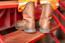 Action Of A Worker Who Wearied With Fully PPE Such As Safety Boots And Coverall Suit Is Standing On The Metal Stair Step. Risk Of Working At Height Concept Photo. Close-up And Selective Focus.