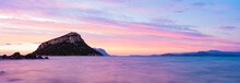 Stunning View Of Figarolo Island During A Romantic And Relaxing Sunrise Reflected On A Calm Water Flowing In The Foreground. Golfo Aranci, Sardinia, Italy.