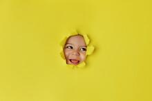 Happy Baby Face Peeking Through Yellow Torn Paper