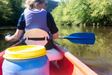 Rear view of a woman wearing a life jacket paddling a canoe down a river in europe
