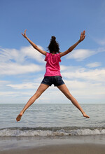 Young Girl Jumping Very High With Open Arms And Legs By The Sea