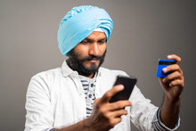 Young Sikh Man Purchasing By Paying Online Using Credit Card In Mobile Phone - Concept Of Online Shopping Or Ordering From E-commerce.