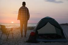 Man Enjoying Sunset Near Camping Tent On Beach, Back View