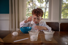 Young Scientist Concentrating On An Experiment Wearing Lab Coat