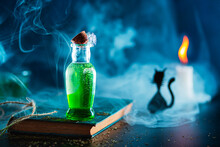 Halloween Bottle With Green Liquid, Stand On An Old Book, Around Is Smoke Or Steam, Scarry Cat Sit Near The Candle With Nice Orange Flame, All Colours Are Green, Blue And Orange. Mystery Atmospheric