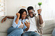 African american couple using cellphone, celebrating win