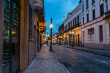Old Center Of The City Of Santos. Street Of Trade. Stone Street, Facades Of Old Houses, Old Cast Iron Poles With Yellow Light And In The Background The Church Of Valongo.