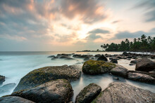 Beautiful Colorful Sunset Over Sea And Boulders Seen Under The Palms On Sri Lanka, Near Matara. Long Exposure Photo.