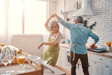 Beautiful Playful Senior Couple In Aprons Dancing And Smiling While Preparing Healthy Dinner At Home