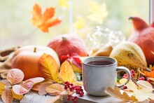 Autumn Still Life With A Beautiful Bokeh. Autumn Leaves And A Cup Of Hot Coffee Or Tea, Orange Pumpkins And An Autumn Harvest. Seasonal, Morning Coffee, Sunday Rest And The Concept Of Still Life