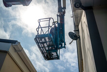 Worker On A Aerial Access Platform, Cherry Picker, Cleaning House