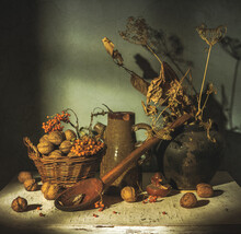 Old Dishes And Dried Plants Are On The Table. There Are Nuts In A Wicker Basket. Forgotten Things.