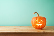 Halloween Jack O Lantern Pumpkin Decoration On Wooden Table. Copy Space For Product Display