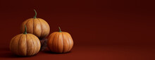 Seasonal Background Banner With Copy-space. Trio Of Pumpkins On Deep Red Color. Fall Concept.