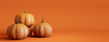 Three Pumpkins On A Orange Colored Background. Autumn Themed Banner With Copy-space.