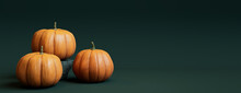 Seasonal Background Banner With Copy-space. Trio Of Pumpkins On Dark Green Color. Autumn Concept.