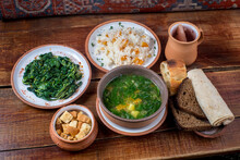 Middle Eastern Cuisine Dishes In Ceramic Plates On A Wooden Table. Soup With Herbs And Vegetables, Rise With Dry Fruites, Roasted Spinach, Rusks, Bread, Lavash, And Compote