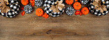 Fall Top Border Of Leaves, Orange, And Black And White Buffalo Plaid Pumpkins Over A Wood Banner Background. Overhead View With Copy Space.