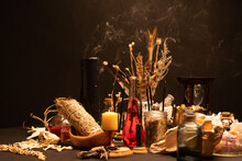 Witchcraft Still Life With Black Burning Candles Selective Focus. Esoteric Gothic And Occult Witch Table For Halloween. Various Magic Objects And Ritual Arrangement. Gothic Halloween.