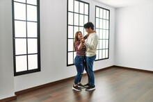 Young Hispanic Couple Smiling Happy Dancing At Empty New Home.