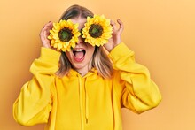 Beautiful Caucasian Woman Holding Yellow Sunflowers Over Eyes Angry And Mad Screaming Frustrated And Furious, Shouting With Anger. Rage And Aggressive Concept.
