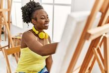 Young African American Artist Woman Using Headphones Drawing At Art Studio.