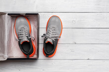 New Pair Of Gray Mesh Fabric Sneakers: One In The Open Box And Other Near On The Grey Wooden Floor. Modern Laced Up Textile Trainers For Sport And Active Lifestyle. New Shoes Box. Copy Space.