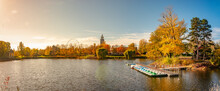 Panoramic View Over City Park Rotehorn And Lake With Tour Boats In Autumn Colors At Sunny Day With Blue Sky At Sunset, Magdeburg, Germany.