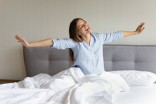 Happy Teen Millennial Girl Feeling Joy, Full Of Energy After Sleep Enough, Awaking. Cheerful Young Woman Sitting In Bed On Comfortable Mattress, Stretching Hands, Body, Smiling With Closed Eyes